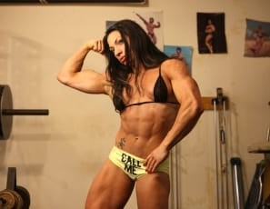 Female bodybuilder and muscle porn star Ripped Vixen is posing for you in the gym, showing off her ripped abs, vascular biceps, powerful pecs and legs, and her tattoos. She takes off her Call Me panties so you can see her big clit and pierced labia in close-up as she masturbates.