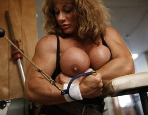 Female Bodybuilder Wild Kat is posing in the gym, showing your her tight glutes and massive legs, and working her pecs and big biceps muscle with cables. Then she starts playing with her big clit, and you get to watch what's on cable in close-up.