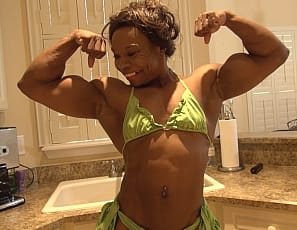 Female bodybuilder and muscle porn star Nadia is posing for you in the kitchen, taking off her panties so you can see the naked ebony muscles of her legs, glutes, abs and biceps, and playing with her ass and masturbatiing her big pink clit while you watch it throb in close-up. It's so hard, she moans. Is yours?