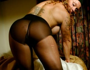 In the bedroom, Petra's panties and black hose are getting in the way of her touching herself, so she starts shredding those stockings while she leaves her high-heeled shoes on. That gives you a nice look at her sexy legs and glutes, and her tattoos – and at her big clit, close up, as she uses the last shred to get off.