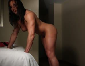 In the bedroom, bodybuilder Italian Muscle is masturbating, enjoying her big clit and the full lips of her pretty pussy – which you can see in close-up  - as well as flexing her biceps as she strokes. Enjoy looking at her bent over and the soles of her bare feet.