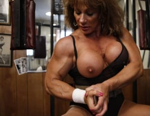 Muscular Wild Kat, posing in the gym in a sheer bodysuit, showing off her glutes, her legs, and a very big clit, so big it takes two hands to hold it. It's even bigger in the close-ups. This Kat has one strokable pussy.