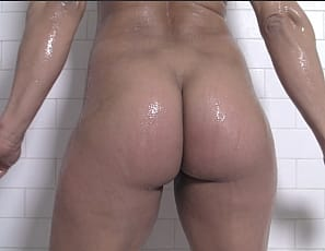 This female bodybuilder prefers to remain anonymous, but she didn't mind us showing you this home movie of her in the shower, soaping up her muscular pecs, legs, glutes, biceps and abs, masturbating her big clit, penetrating herself with a toy and playing with her ass.