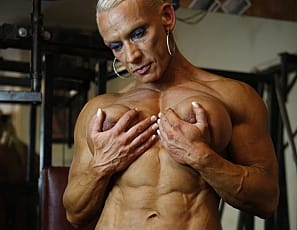 Bodybuilder Nicole Savage likes to work out in the gym in the nude and barefoot – a great way to check out her incredible definition and vascularity from every angle as she does bicep curls and poses, then stretches her glutes and legs and gives you a close-up look at her pierced and well-developed big clit.